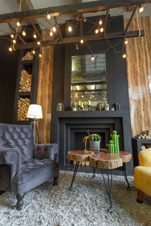 dark brutal interior of sitting room decorated with wooden logs. yellow and gray soft armchairs, huge arc window and fireplace