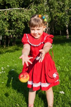Portrait of young laughing girl throwing up red apples