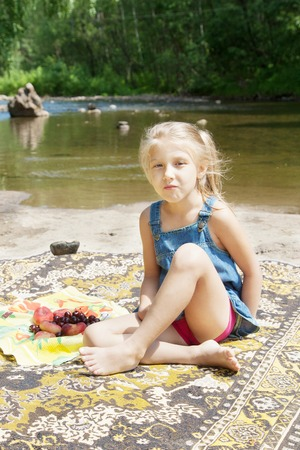 Smiling little girl having picknick on the riverside