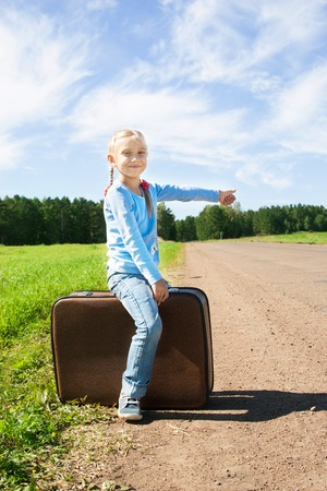 Lonely girl with suitcase near the road  photo