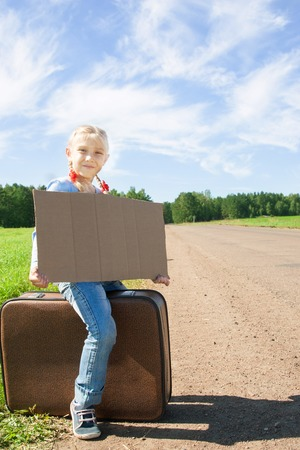Lonely girl with suitcase standing near the road and holding a board. photo