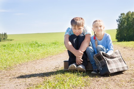 cute girl and boy with suitcase on road photo