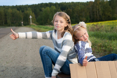 Two Lonely girls with suitcase standing about road and holding paper with copy space in hands photo