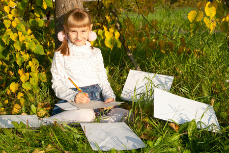 Beautiful girl reading letter while sitting on the tree on sunny  day. photo