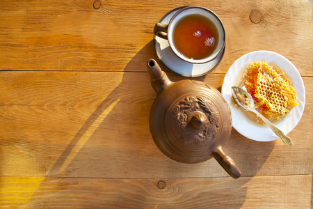Composition with tea in cup and teapot on table, on wooden background photo
