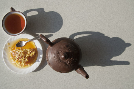 Composition with tea in cup and teapot on table, on  white background photo