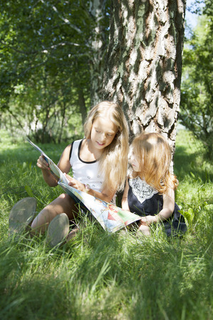 sisters reading the book on picnic in summer park photo