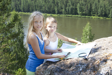 Two Young Girls Tourists  in Mountain read the Map near  River photo