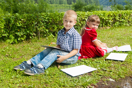 Happy Young girl and boy Writing letter, Smiling in summer Garden. photo
