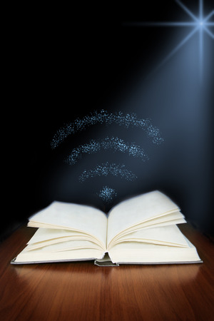 Old open book with magic wi - fi   on wood planks and dark abstract background photo