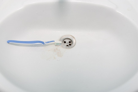 periodontics: bloody toothbrush lies in a washbasin. dental concept