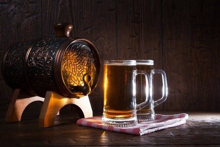unbottled: Beer mugs and barrel on a wooden background. Stock Photo