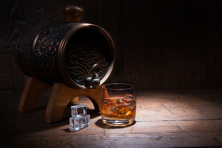 distilled alcohol: Glass of whiskey  with ice  beside a barrel on  wooden background. Stock Photo