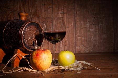 tabel: Apple , glass of red wine and barrel on rustic wood tabel.