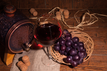tabel: Glass of red wine and barrel on rustic wood tabel.