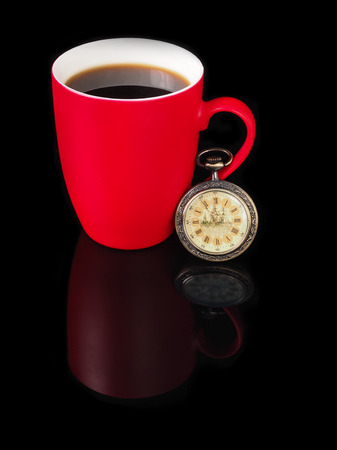 morning breakfast: Vintage watch and red cup with reflection on black background.