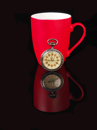 morning coffee: Vintage watch and red cup with reflection on black background.
