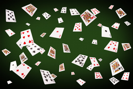 Playing cards flying at the poker table. Imagens