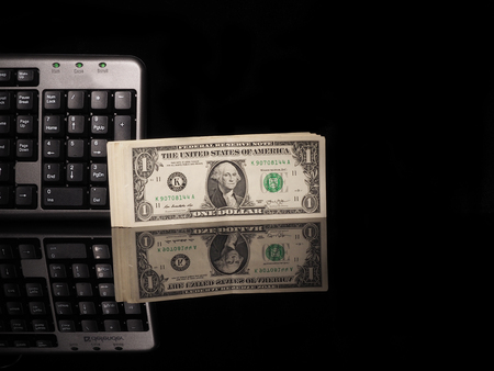 fraudster: Dollar bills and keyboard on a black background with reflection.