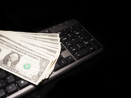 web scam: Dollar bills and keyboard on a black background with reflection.