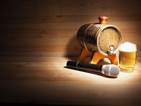 Barrel and glass of beer, microphone on wooden background. concept karaoke.