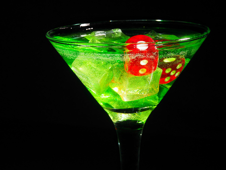 Red dice in a cocktail glass on black background. casino series. Stock Photo