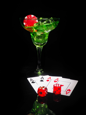 Red dice and a cocktail glass on black background. casino series. Фото со стока