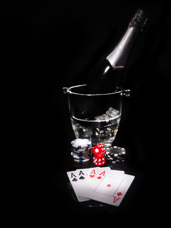 Playing cards and a bottle of champagne in bucket.