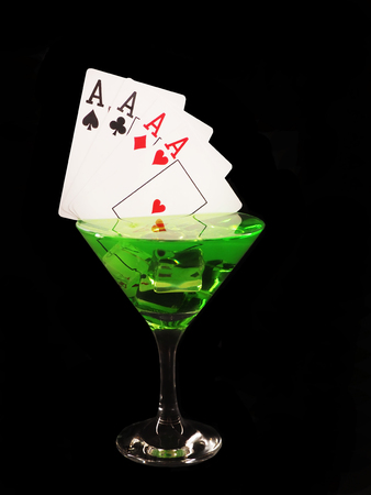 Playing card in a cocktail glass on black background. casino series. Stock Photo
