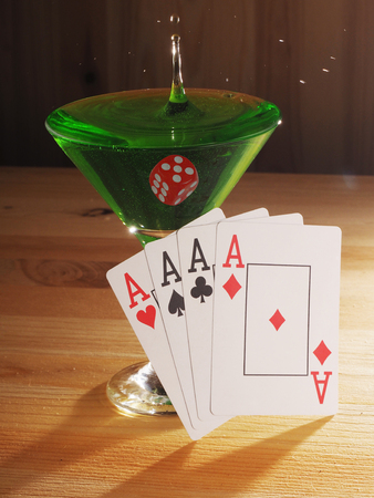 Glass with a cocktail and playing cards . wooden background.