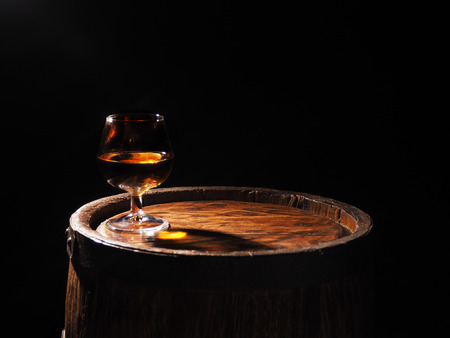 Glass of cognac with barrel on wooden backgroun.