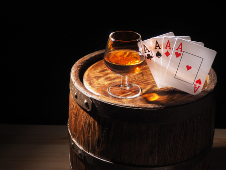 Playing cards and wine glass of cognac on barrel. Stock Photo