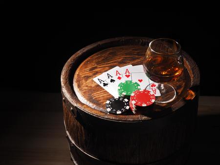 Jeux de cartes et un verre de vin de cognac sur le baril.