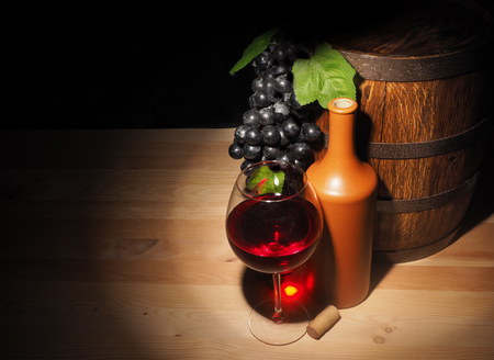 Glass of red wine and barrel on wooden table. Stock Photo