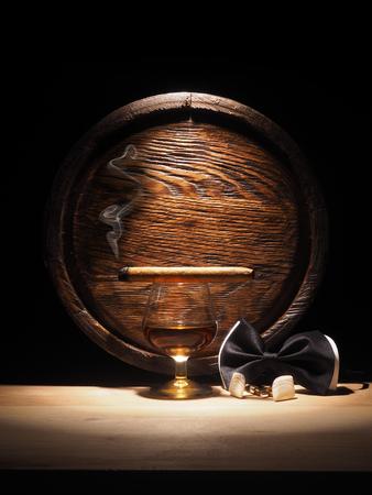 Glass of Cognac , Cigar and old oak barrel. Stock Photo