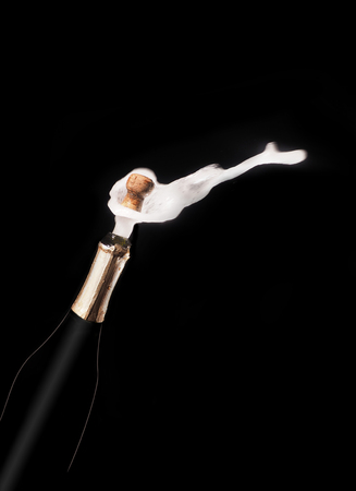 Champagne bottle and spray on black backgroun. Stock Photo