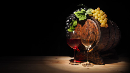 Glass of red , white wine and barrel on wooden table.