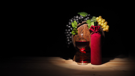 Glass of wine and barrel on wooden table.