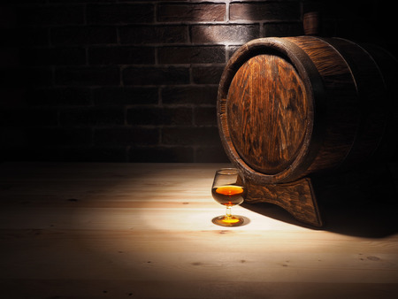 Glass of cognac with barrel on wooden table.