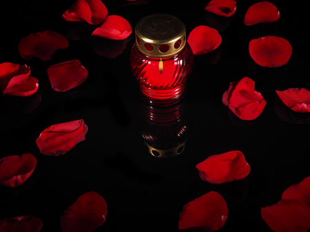 Burning candle in a red glass candlestick.