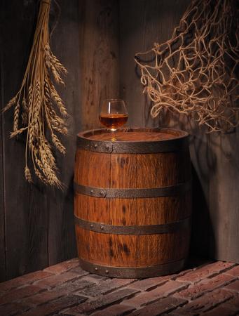 Glass of cognac with barrel in cozy cellar.