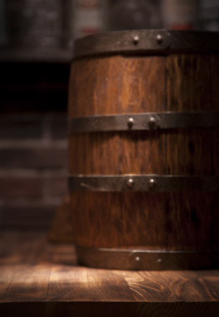Barrel of whiskey on rustic table.blur bar background.