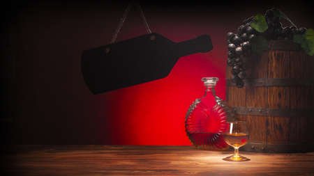 Glass of cognac with barrel on red backgroun.
