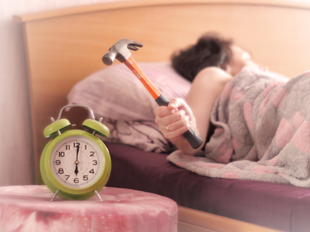 beating the alarm clock with hammer. concept of sleep.