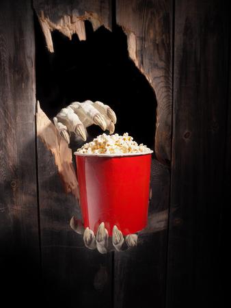 Zombiehand door gat dat in rustiek hout is gebarsten. Halloween-thema. Stockfoto