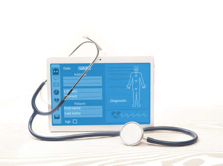 White tablet and stethoscope on background. Online medical support concept. Banque d'images