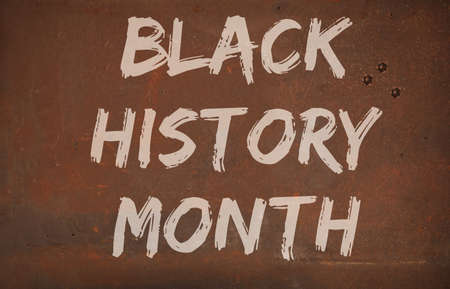 February is Black History Month. Sign on rustic background.