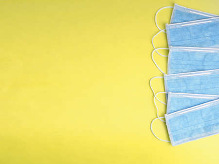 Blue medical masks on yellow background. Medical concept. Flat lay with copy space.