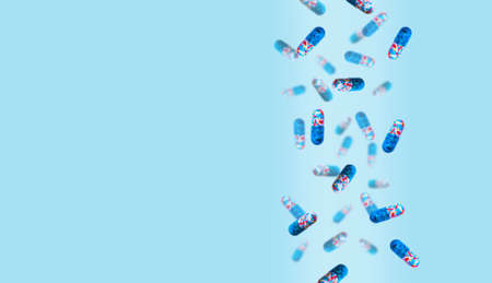 Colored pills are falling against a colored background. Medicine and healthcare concept