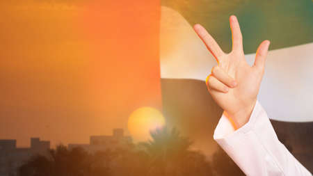 UAE National day - 3 fingers sign of Sheikh Mohammed bin Rashid, with UAE Flag on the background. patriotism concept